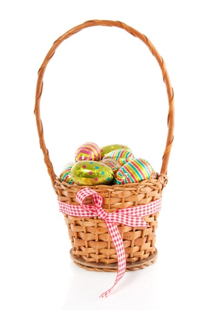 colorful easter eggs in a wicker basket with a checkered ribbon isolated over white photo