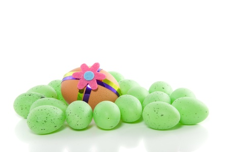 a colorful decorated easter egg between a lot of green plastic eggs isolated over white Stock Photo
