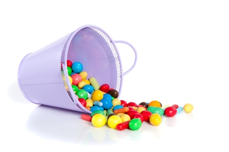 a purple overturned pot full of colorful sweet candy isolated over white