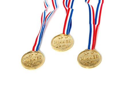 three golden medals on colored ribbons photo