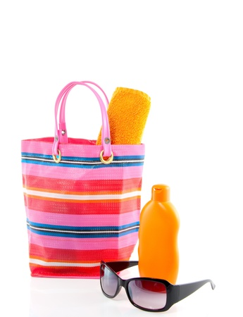 a beachbag with sunscreen and sunglasses isolated over white Stock Photo