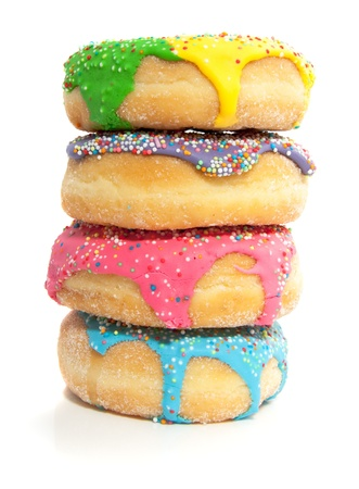 four colorful vertical donuts with speckels on top