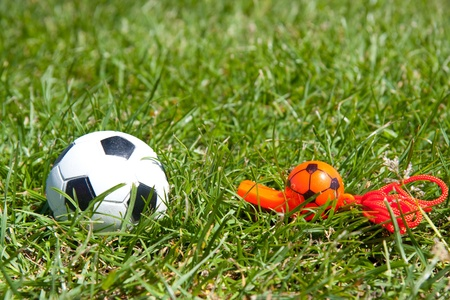 a football and a referees whistle on a green lawn photo