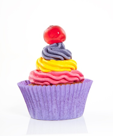 a tricolor creamed cupcake  with a cherry on top isolated on white