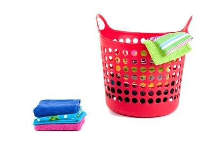 plastic red laundry basket with folded laundry isolated on white background photo