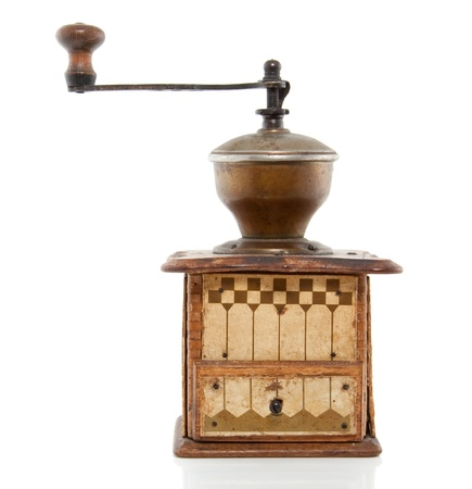 an antique coffeegrinder with a little drawer isolated over white