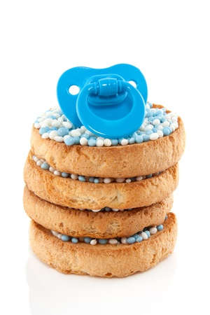 a blue babys comforter on top of a stack of Dutch bicuits with blue white rusk isolated over white