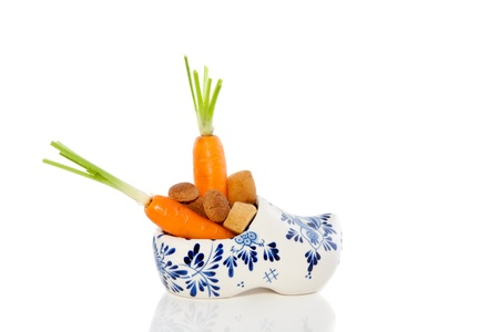 carrot in a shoe for the horse of Sinterklaas decorated with ginger-nuts isolated Stock Photo - 15071876