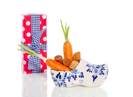 carrot in a shoe for the horse of Sinterklaas decorated with a gift and ginger-nuts isolated photo
