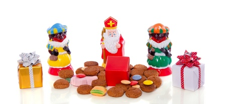 Traditional Dutch Sinterklaas and Piet with gingernuts and gifts to celebrate five december isolated over white background