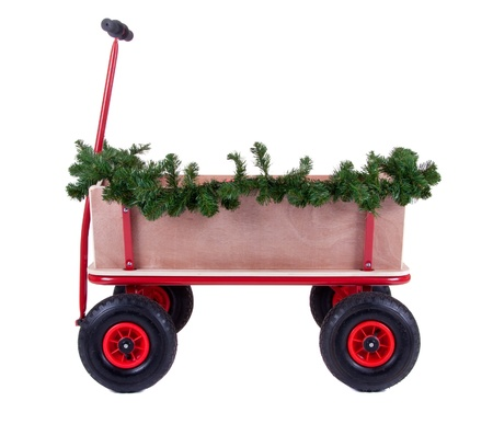 a wooden transport wagon decorated with christmas branch isolated over white