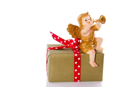 a musical angel on top of a present isolated on white background