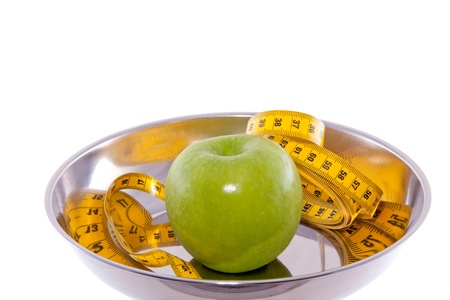 an apple with measure tape in a chrome bowl isolated over white