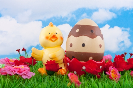 a chick egg shell with an easter egg on a green lawn with flowers against a blue cloudy sky Stock Photo