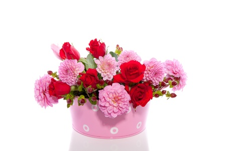 red and pink bouquet in a pink iron bucket isolated over white photo