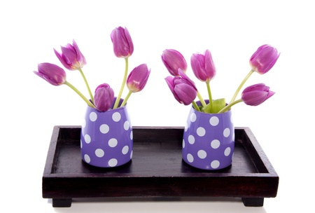 two little vases with purple tulips on a wooden tray isolated over white