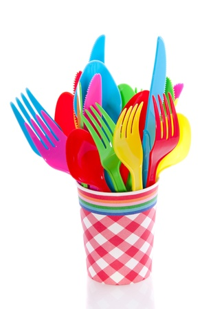 colorful plastic cutlery in a checkered red white cup isolated over white