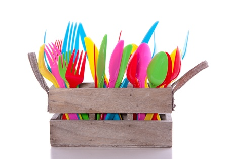 colorful plastic cutlery in a wooden crate isolated over white photo
