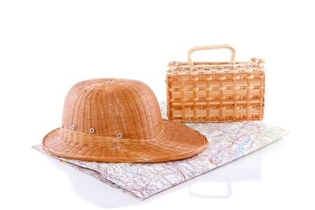 a straw hat and a wicker trunk on a map isolated over white
