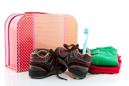 a colorful spare suitcase  with shoes and cloths isolated over white