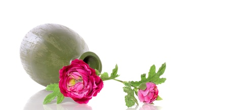 Silk pink flower buttercup in a green earthenware horizontal vase isolated over white background