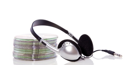 a silver black headphone and a pile of cd and dvd drives isolated over white Stock Photo