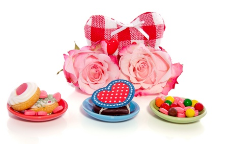 valentine hearts with pink roses and candy and cookies isolated over white