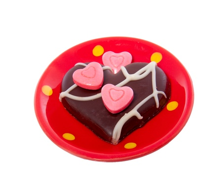 a lovely chocolate heart decorated white pink hearted candy on a ceramic little saucer isolated over white