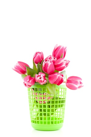 a bundle of pink tulips in a green shopping bag isolated over white