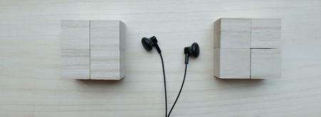 earpiece: Black earphones over wooden board Stock Photo