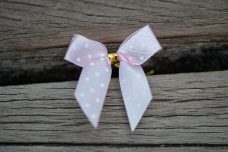 moño rosa: Lazo rosa sobre fondo de madera