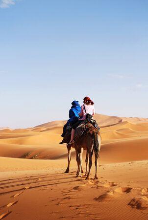 Berber man leading camel and tourist traveller through the Saharan Desert near Erg Chebbi in Morocco