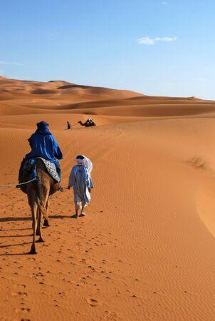 Berber man leading camel and traveller through the Saharan Desert near Erg Chebbi in Morocco