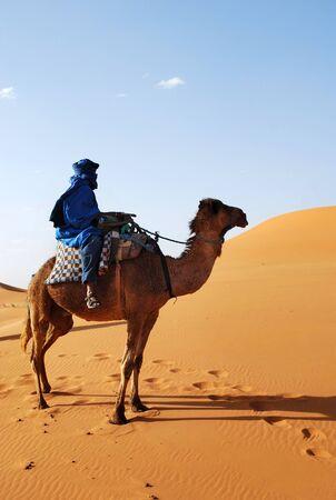 Berber man riding camel through the Saharan Desert in blue near Erg Chebbi in Morocco