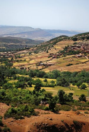 Farming fields and hills in the Rif Mountains of Morocco with a distant old town with traditional mud buildings