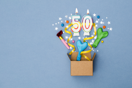 Number 50 celebration present background. Gift box exploding with party decorations 스톡 콘텐츠