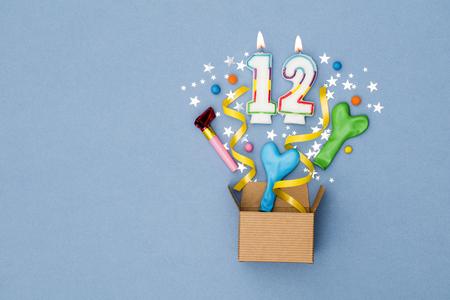 Nummer 12 viering huidige achtergrond. Geschenkdoos ontploft met feestdecoraties