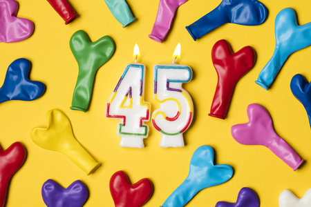 Number 45 candle with party balloons on a bright yellow background