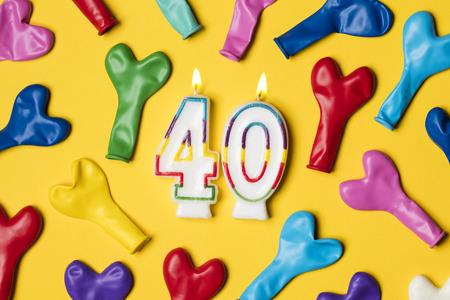 밝은 노란색 배경에 파티 풍선과 함께 번호 40 촛불 스톡 콘텐츠
