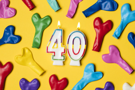 Number 40 candle with party balloons on a bright yellow background Banco de Imagens