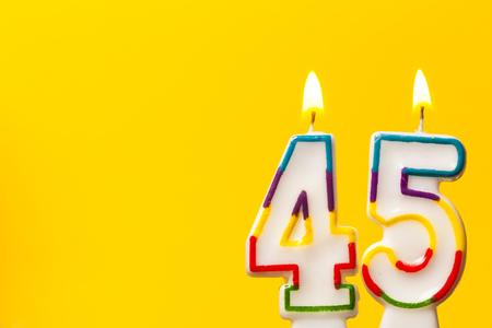 밝은 노란색 배경으로 생일 축하 촛불 45 번