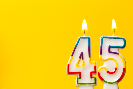 Number 45 birthday celebration candle against a bright yellow background