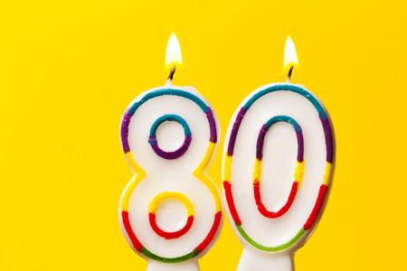 Number 80 birthday celebration candle against a bright yellow background Archivio Fotografico