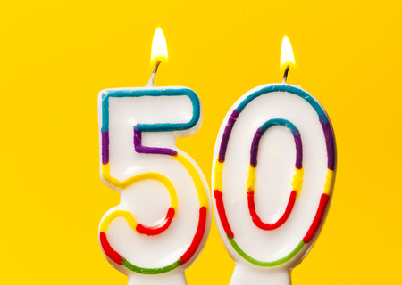 Number 50 birthday celebration candle against a bright yellow background Stockfoto