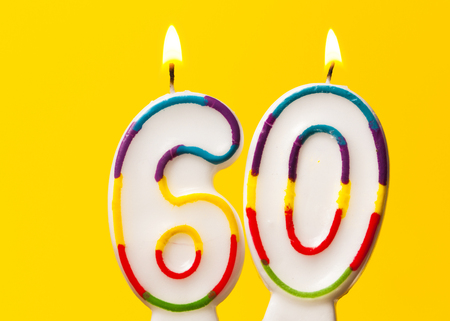 Number 60 birthday celebration candle against a bright yellow background