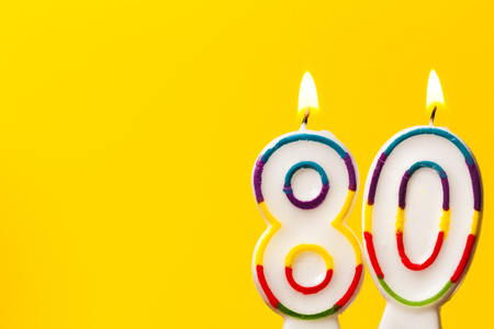 Number 80 birthday celebration candle against a bright yellow background Stockfoto