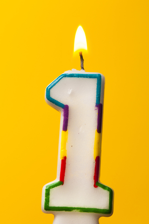 Number 1 birthday celebration candle against a bright yellow background Zdjęcie Seryjne