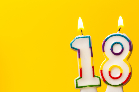 Number 18 birthday celebration candle against a bright yellow background