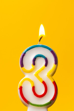 Number 3 birthday celebration candle against a bright yellow background