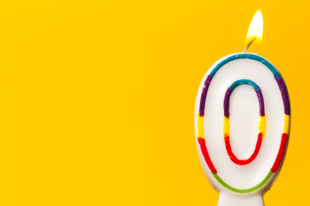 Number 0 birthday celebration candle against a bright yellow background